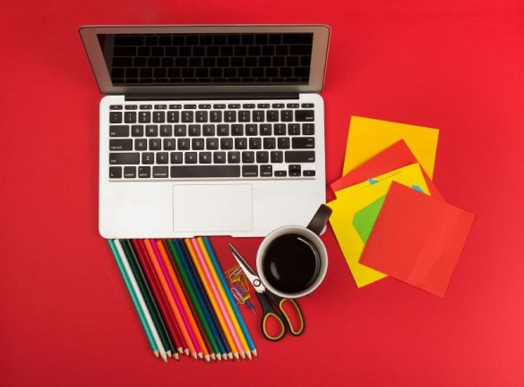 Creative messy workplace with laptop and stationery